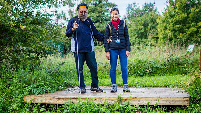 Pardeep holds his cane and arm of his sighted guide Sophia, they look over a lake