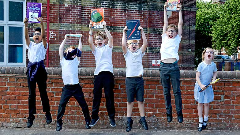 Six children jump holding their CustomEyes books above their heads
