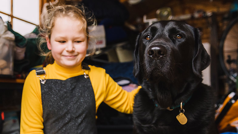 Little girl Oashia smiles next to her black labdrador buddy dog Garston