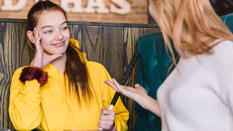 Teenage girl Mia smiles whilst holding her cane talking to a friend in a cafe