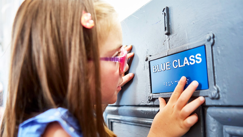 Nell touches braille on her classroom door that reads blue class