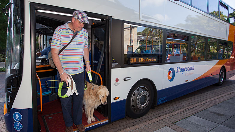 Man-with-guide-dog-getting-off-bus-Guide-Dogs