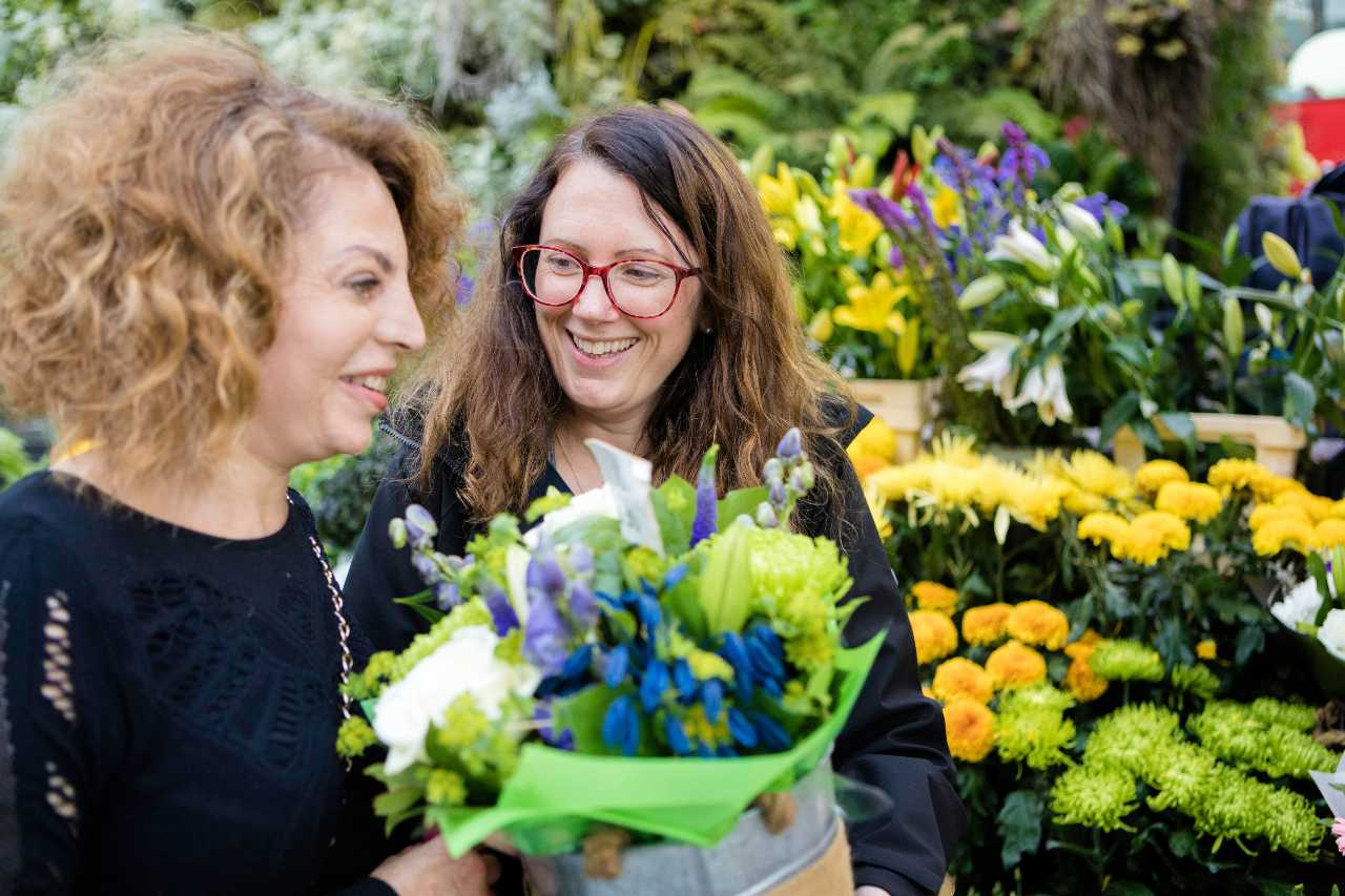 My Guide volunteer presenting flowers to a service user at a flower shop