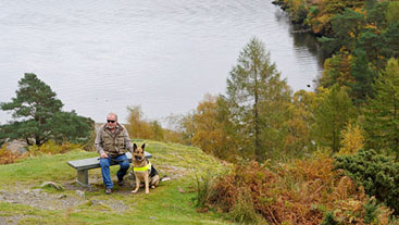Guide dog owner and guide dog sitting on a bench by a lake