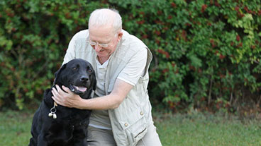 Guide dog owner hugging his guide dog