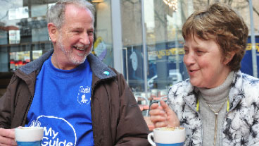 My guide volunteer and a service user drinking a hot drink