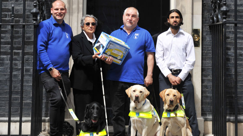 Four campaigners and three Guide Dogs stood outside 10 Downing Street