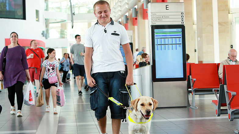 Nathan and guide dog Hudson walk through train station