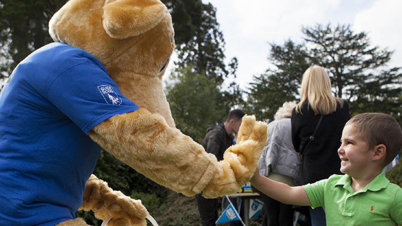 Boy giving a high five to a guide dog mascot