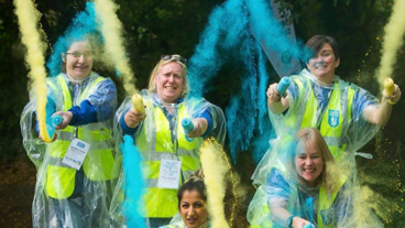 Guide dogs volunteers throwing powdered paint into the air