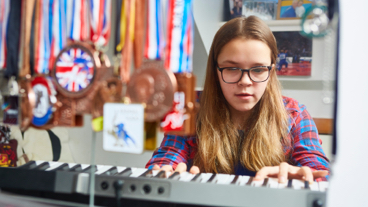 Young girl playing the keyboard with lots of medals hanging behind her