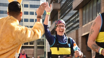 A runner high fives a supporter in fancy dress