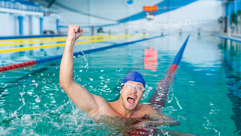 Man raising arm in the air triumphantly while swimming
