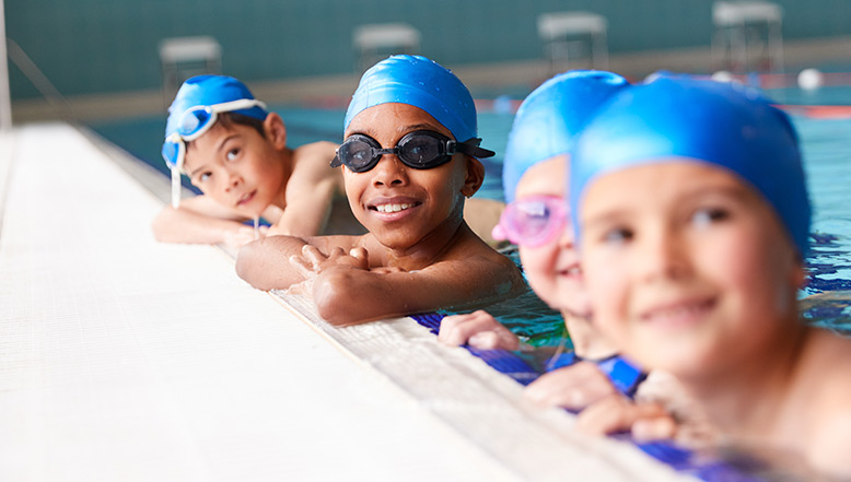 Group of children smiling in a swimming pool wearing swimming hats