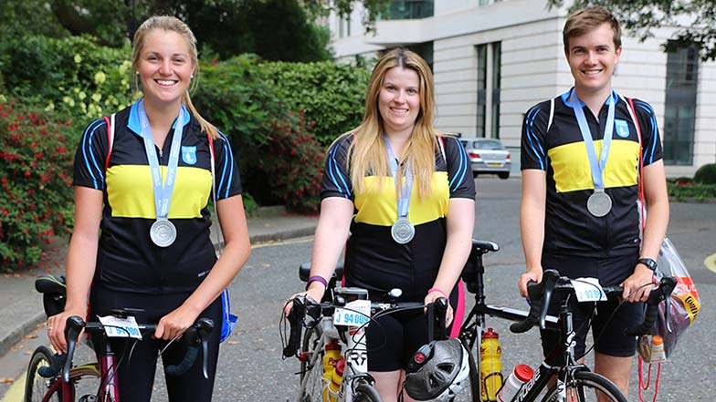 Three-cyclists-with-their-bikes-wearing-medals
