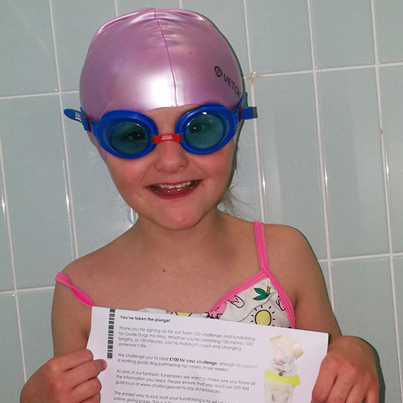 Zannah in her swimming hat with Swim 100 certificate