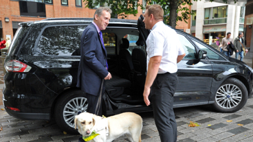Guide dog owner talking to a taxi driver