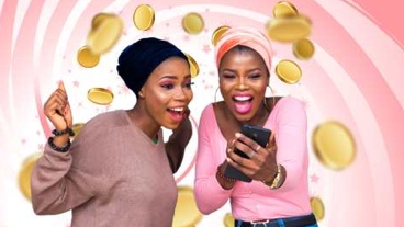 Two women looking at a phone as coins falling on a lucky lottery backdrop