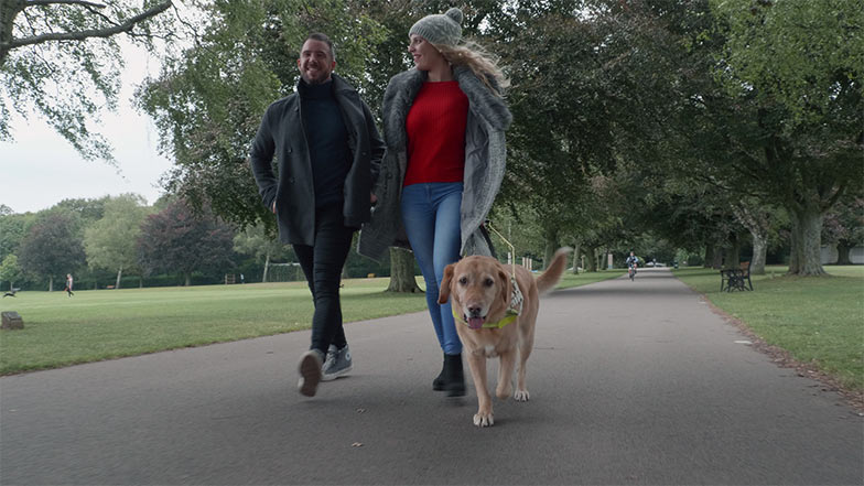 Guide dog owner Stacey walking with a friend in a park