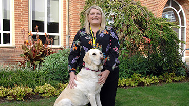 Smiling guide dog owner sitting with her guide dog
