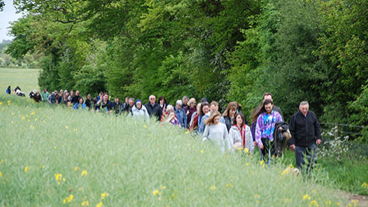 A group of people in the countryside walking in memory