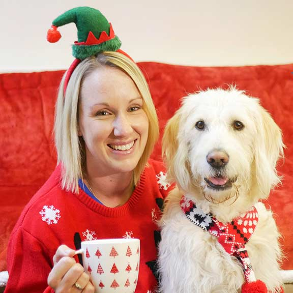 Woman with festive hat and jumper sitting next to a Guide Dog wearing a scarf