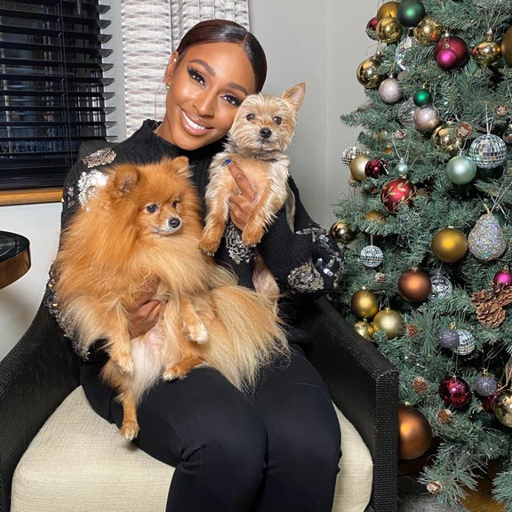Alexandra Burke smiles with her two dogs next to the Christmas tree