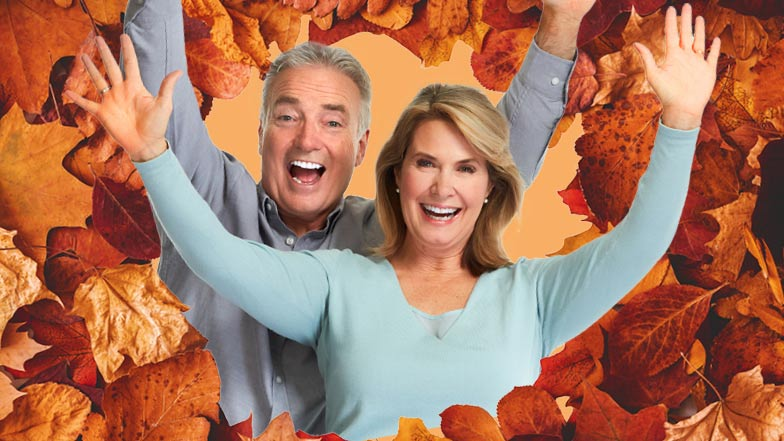Man and woman with their arms in the air surrounded by Autumn leaves