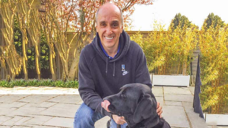 Guide dog owner and guide dog sitting together in a garden