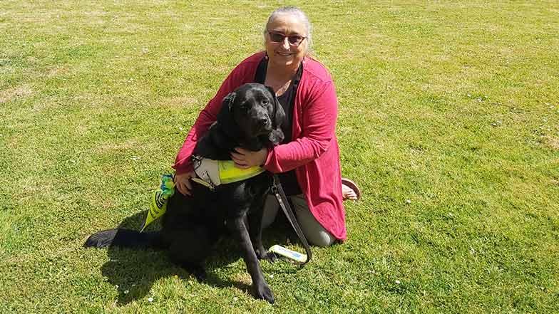 Guide dog owner sitting with her guide dog on grass