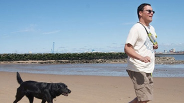 A guide dog owner is walking with his guide dog along the beach