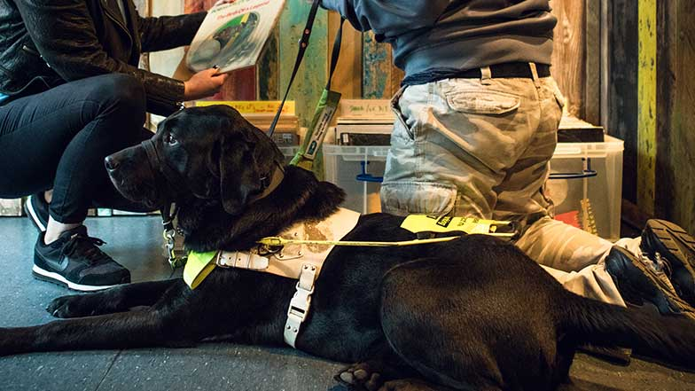 A-guide-dog-with-two-teenagers-in-a-record-shop
