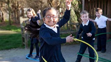 A young school girl plays with a hula hoop while other children watch her