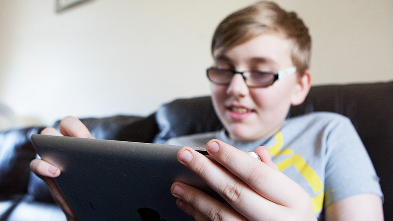Child looks at his ipad smiling