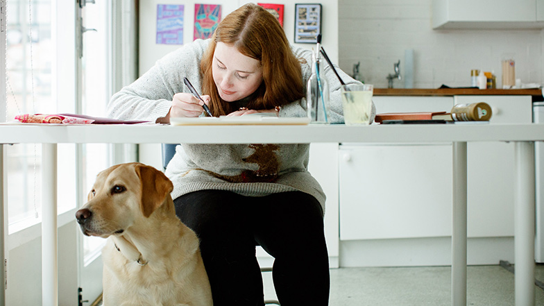 Woman sitting at desk with dog sitting at her feet