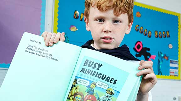 A boy proudly showing his CustomEyes book from Guide Dogs