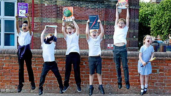 Children in their school's MeteorEyes Club jumping for joy with their CustomEyes books from Guide Dogs