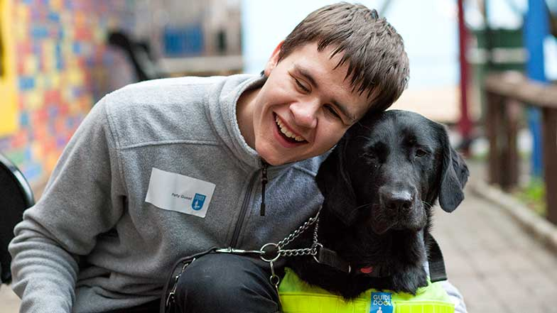 A boy hugging a guide dog at a Guide Dogs' experience day