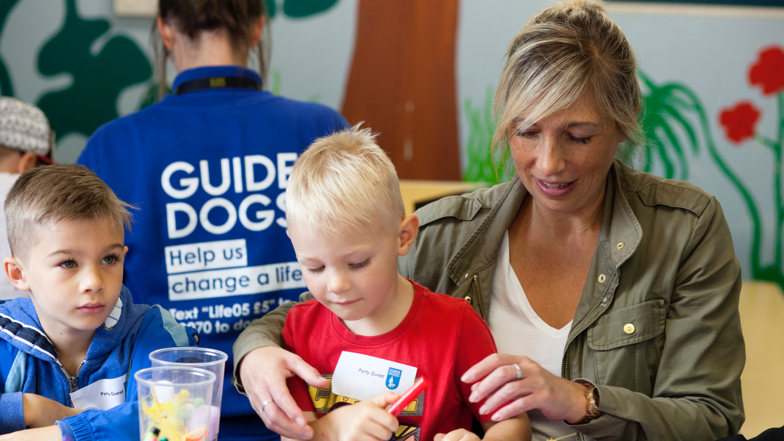 Two children learning about Guide Dogs with a volunteer