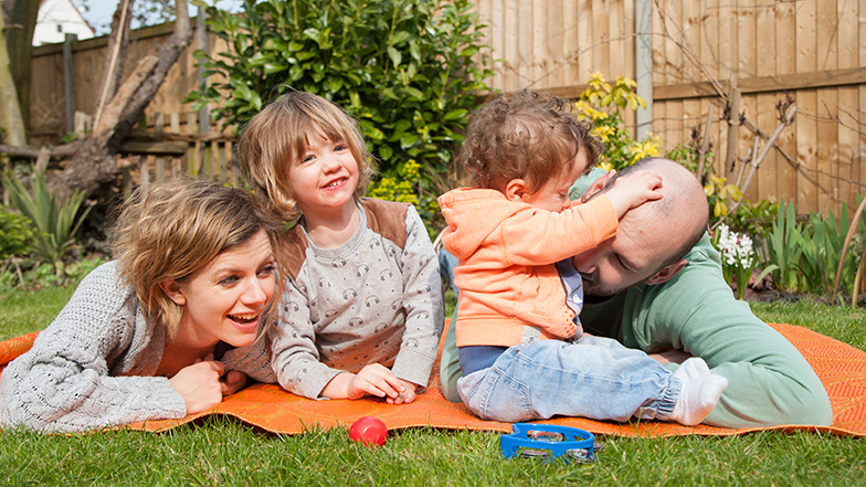 Family in a garden lying down on a mat and playing Guide Dogs