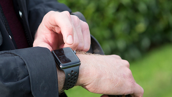 Image shows a man's arm with a smart watch, with the other hand pressing the screen