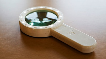 A white, illuminated hand held magnifier on a table