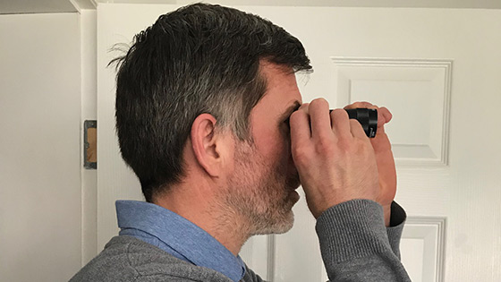 Side view of a man using a monocular